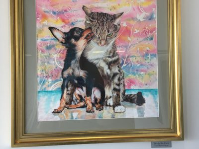 A painting of a chihuahua puppy licking a grey and black striped cat